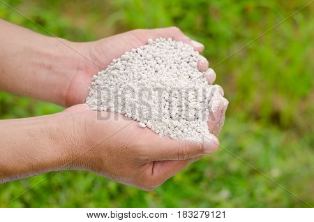 Farmer hand holding plant chemical fertilizer over green background