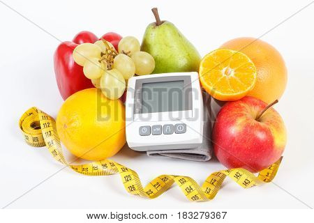Blood pressure monitor fresh fruits with vegetables and tape measure healthy lifestyle slimming and prevention of hypertension concept