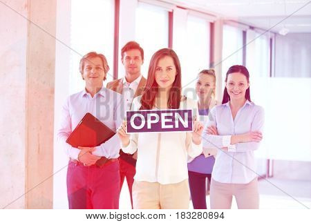Portrait of young businesswoman holding open sign with team behind at office