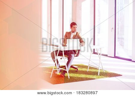 Full length of young businessman with laptop at desk on turf in new office