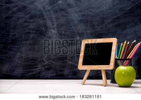School And Office Supplies And Apple In Front Of Blackboard.