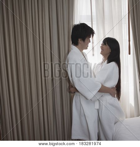 Asian couple in bathrobes hugging in hotel room