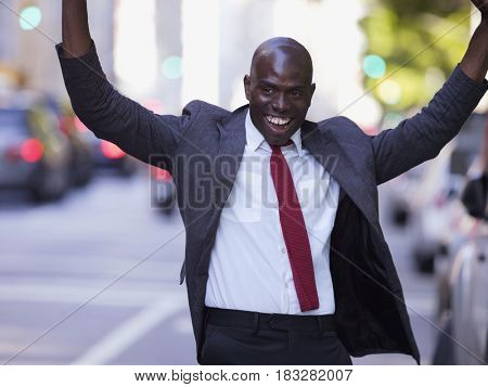 African businessman smiling with arms raised