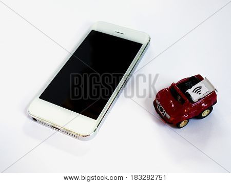 A white smart phone sim card tray and small paper simulated as a SIM card on a red toy car with white background