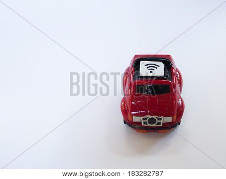Sim card tray and small paper simulated as a SIM card on a red toy car with white background. Wifi symbol on paper sim card