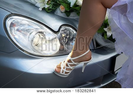 A female foot in a slipper. The leg is on the bumper of the car