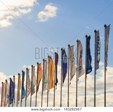 GOMEL BELARUS - 16 April 2017: Many flags on flagpoles in the wind.