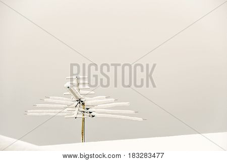 Television antenna covered with snow on a snow-covered roof