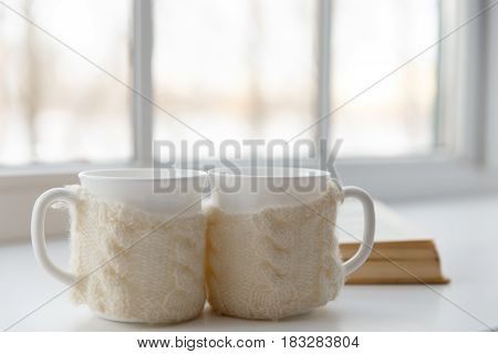 Two White Mugs In A Scarf Stand On A Table In The Background Of A Window With Cozy Aroma Of Coffee.
