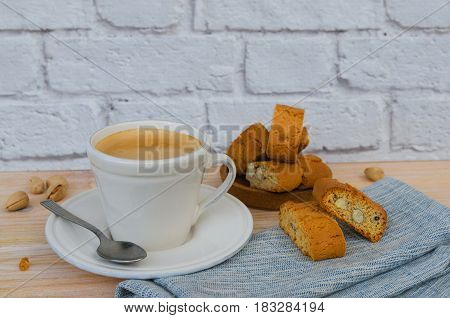 Homemade biscotti cantuccini or cantucci Italian almond sweets biscuits (cookies) served with cup of coffee on wooden background.