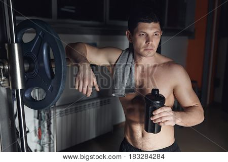 guy bodybuilder tired in gym hold shaker with sportive nutrition - protein of shaker