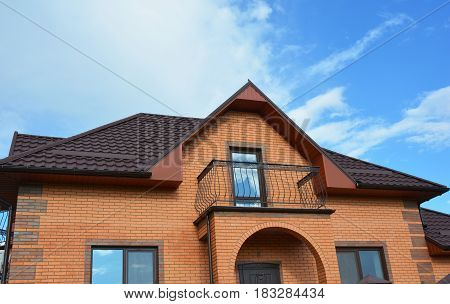 Building brick house construction with different types of attic roof design and metal balcony