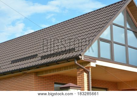 Building Modern House Construction with metal roof rain gutter system and roof protection from snow snow bar (Snow guard). Roof Snow Guards: Building Materials & Supplies. Attic skylight window.