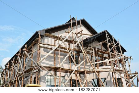 Repair Painting and Plastering Exterior House Scaffolding Outdoor. Stucco Facade Home. Exterior Stucco - Building Conservation.