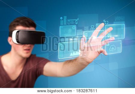 Young impressed man wearing virtual reality goggles with blue squares containing data at his fingers