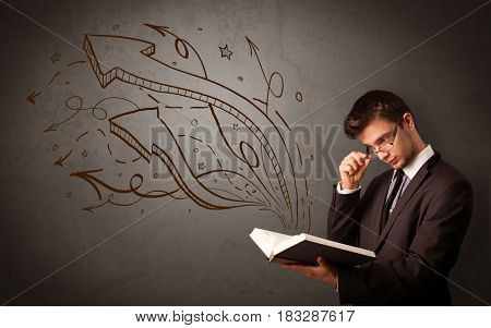 Casual young man holding book with brown arrows and stars flying out of it