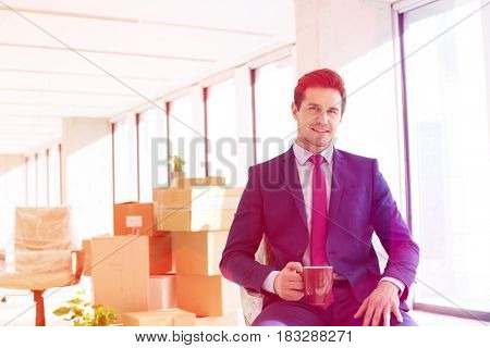 Portrait of young businessman having coffee with moving boxes in background at office