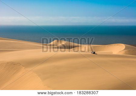 Magical jeep - safari through the sand dunes on the ocean coast. Atlantic shore of Namibia, south of Africa. The concept of exotic and extreme travel