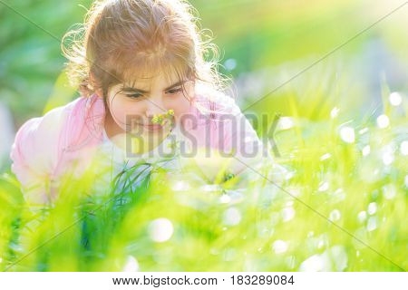 Portrait of a little dreamy girl having fun outdoors in nice sunny day, enjoying aroma of a little flower on the backyard
