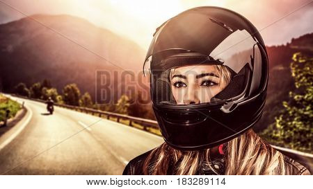 Closeup portrait of a beautiful woman wearing helmet, biker on the mountainous road in mild sunset light, fashion look of motorcyclist girl