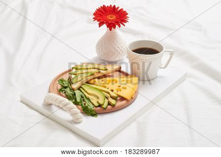 Close-up of useful breakfast rich in vitamins with tasty black tea, juicy green avocado and aromatic cheddar, salad