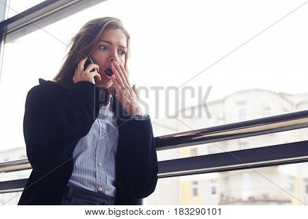 Low angle of shocked businesswoman covering mouth with hand during phone conversation