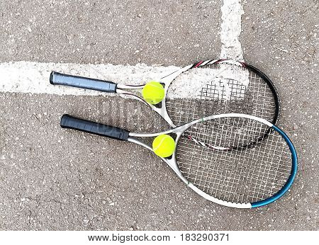 Tennis. Two tennis racquets and two tennis balls.