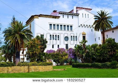 Spanish Colonial style historical building surrounded by lush landscaping taken at the Santa Barbara Courthouse in Santa Barbara, CA