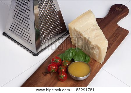 Parmesan cheese, still life italian food. Still life with parmesan cheese, grater, honey, cherry tomatoes and basil on a wooden chopping board.