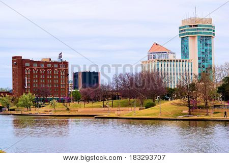 March 20, 2017 in Wichita, KS:  Downtown skyline beside the Arkansas River taken in Wichita, KS where people can walk beside the river on a pedestrian trail while viewing the downtown skyline