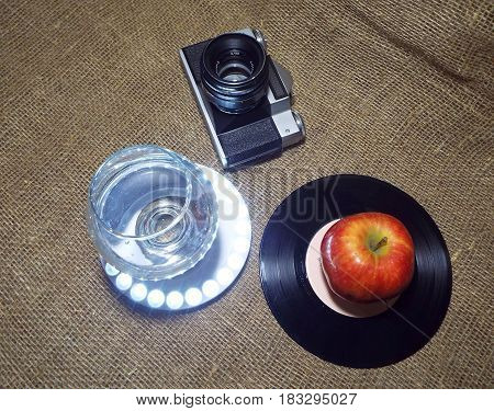 Retro still life - film camera, a glass of water and vinyl records
