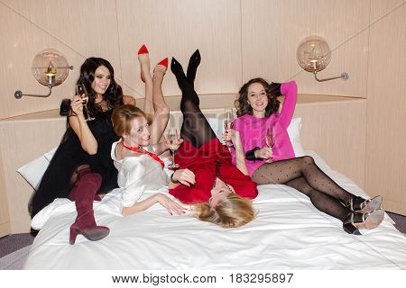 Pretty four female friends lying with champagne on the bed. Horizontal indoors shot.