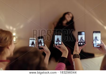 Horizontal indoors shot of group of women taking shots of their posing friend.