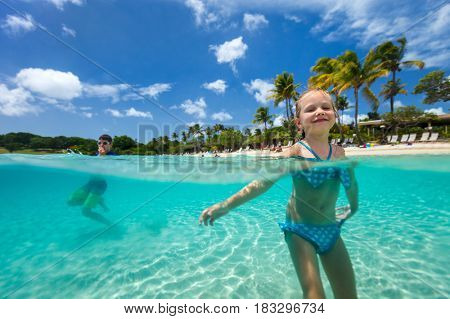 Split underwater photo of adorable little girl and cute boy splashing in a tropical ocean water during summer vacation