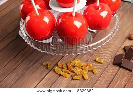 Glass stand with delicious toffee apples on wooden background
