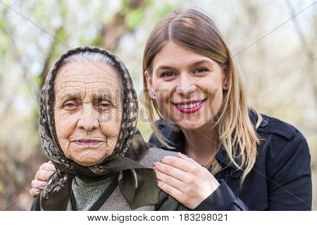 Picture of a happy senior lady posing in the garden with her beautiful granddaughter