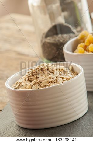 bowl of oat flakes close up on wooden table