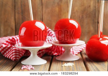 Delicious toffee apples on stands against wooden background