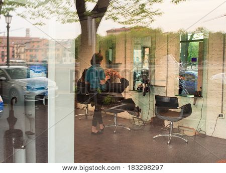 VERONA ITALY - APRIL 07: Woman is getting her hair straightened at beauty saloon on April 07 2017
