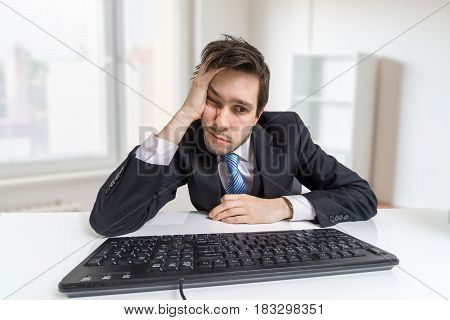 Overworked And Tired Businessman Is Working With Computer In Off