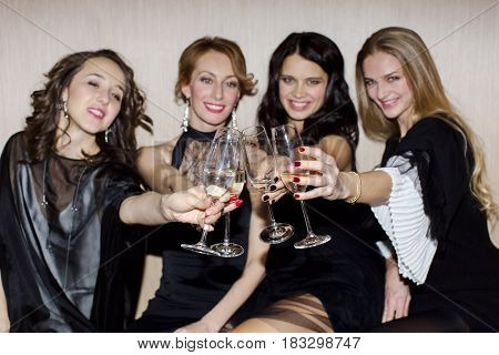 Cheerful female friends clanging glasses with champagne and smiling. Horizontal indoors shot.