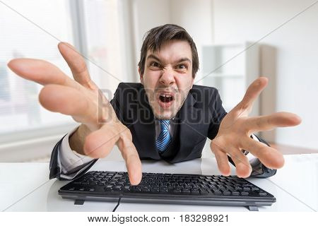 Confused Angry Businessman Is Working With Computer In Office.