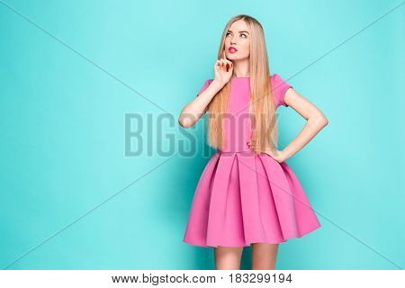 Smiling beautiful young woman in pink mini dress posing and looking away. Three quarter length studio shot on blue background.