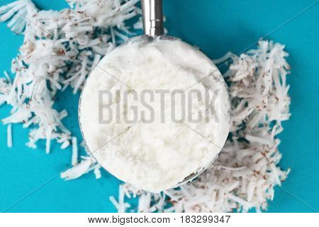 Metal scoop with fresh ice cream and heap of desiccated coconut on color background