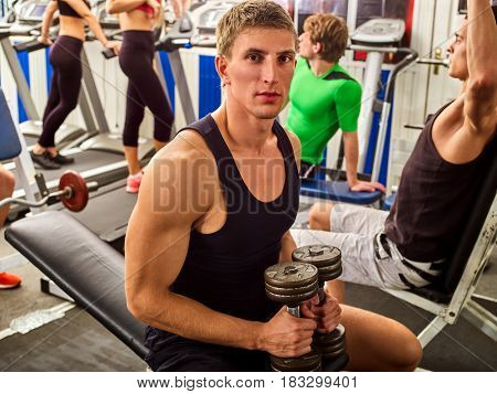 Friends in gym workout with fitness equipment. Man holding dumbbell workout at gym. Group people working on simulator body and running on treadmill at gym. Handsome guy in foreground looks at camera