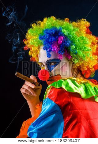Mad clown on black background. Woman is smoking cigar. Portrait of crazy female with an angry look after performance.