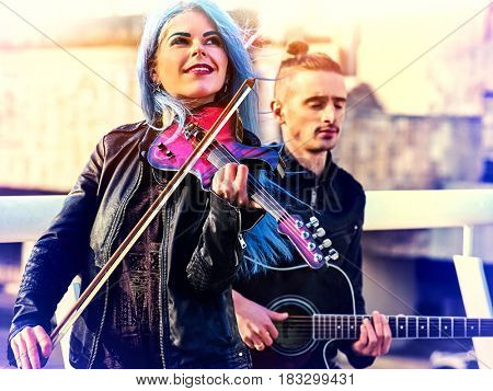 Playing viola woman and man perform music on violin and guitar in city outdoor. Girl with blue hairstyle and eyebrows performing jazz on urban street .