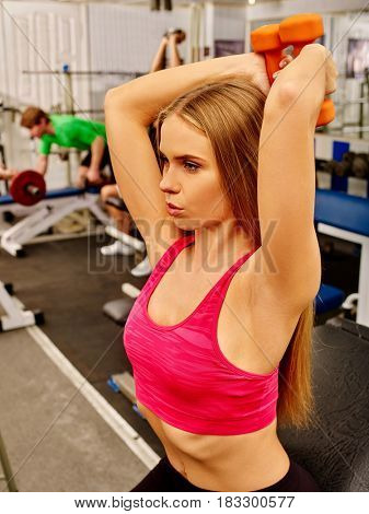 Woman holding dumbbell workout at gym. Top view of middle section of bare belly. Set of heavy orange dumbbells on background. Man with barbell in background. Body that you want concept.