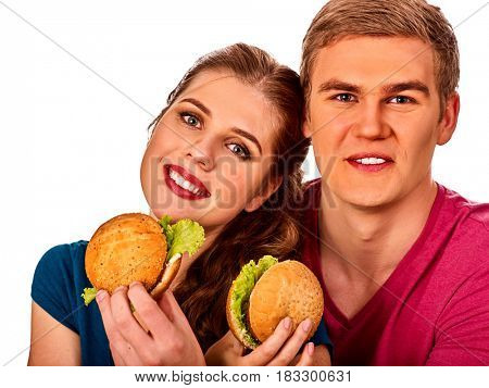 Couple eating in fast food restaurant. Man and woman eat hamburger with ham . Friends holding two burder junk on white background isolated.