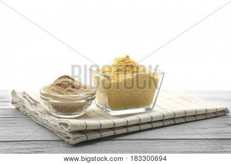 Composition with flour on wooden table against white background